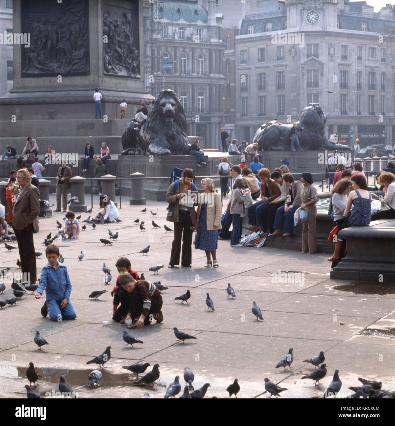 Les touristes typique nourrir les pigeons autour d'Edwin Landseer's lions à la base de la Colonne Nelson Photo Stock