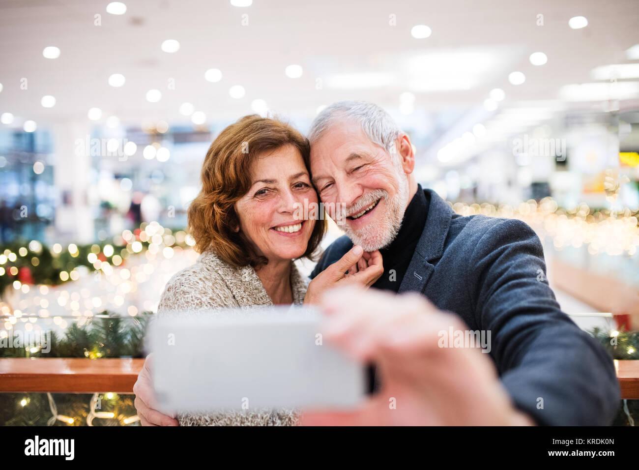 Senior couple with smartphone faisant des achats de Noël. Photo Stock