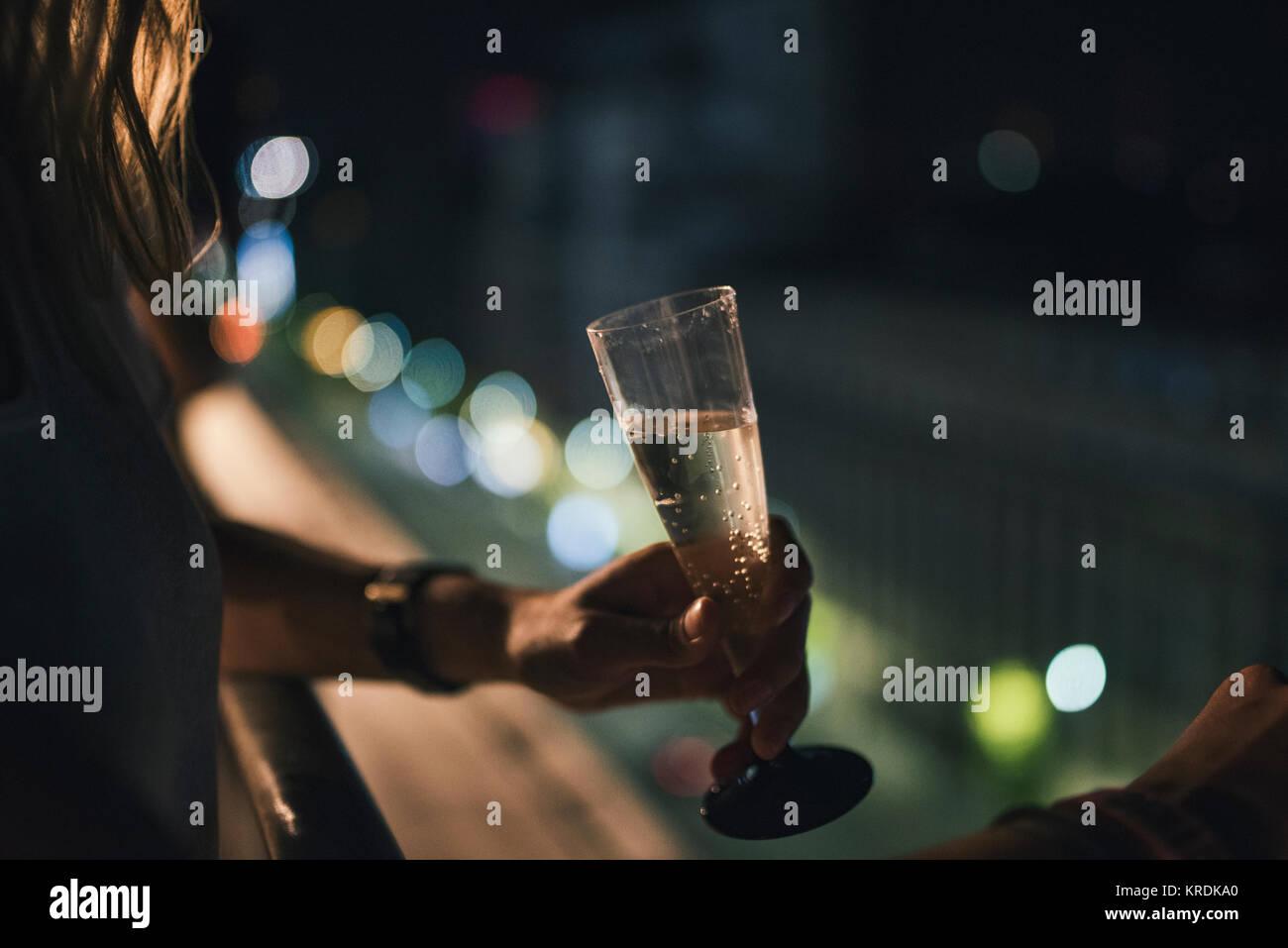 Gril avec un verre de champagne avec les lumières de la ville historique Photo Stock