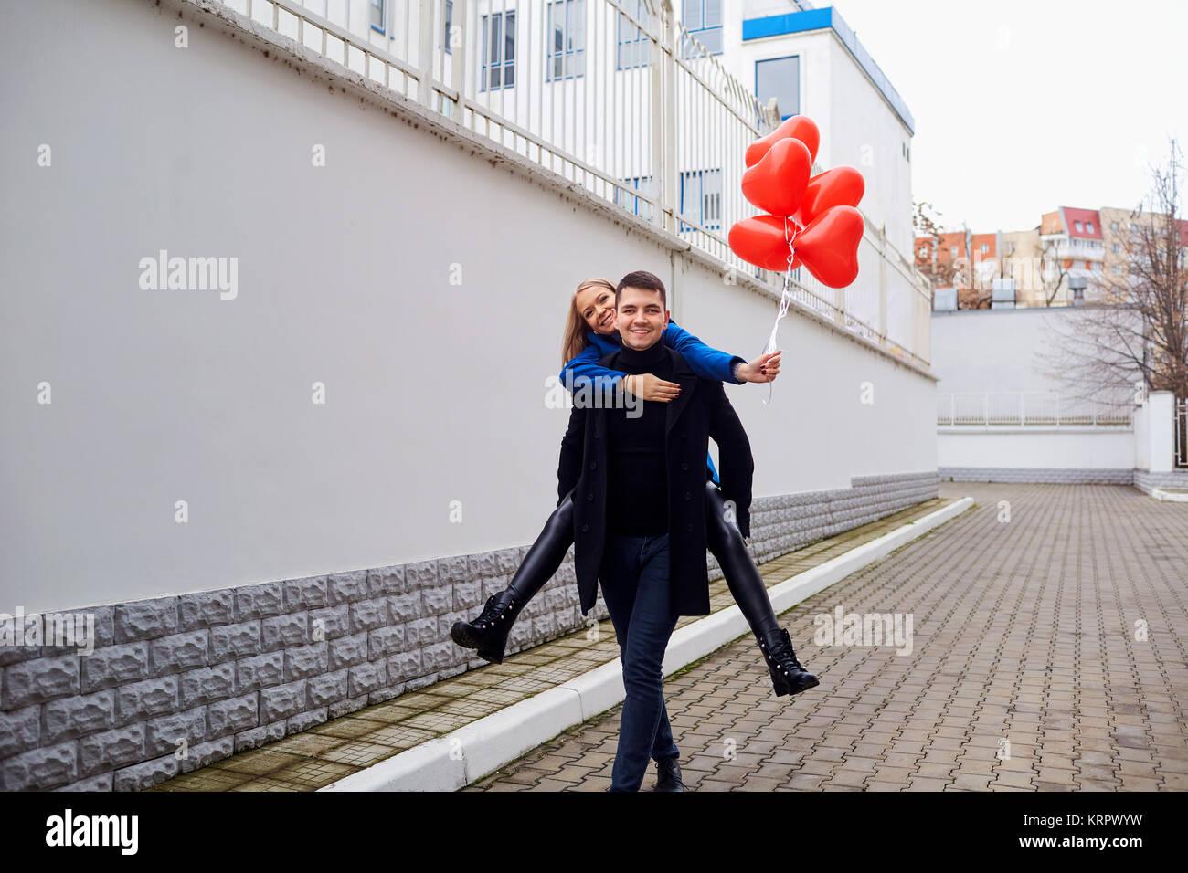 Fille sur le dos de gars avec des ballons coeur rouge dans la rue. Photo Stock