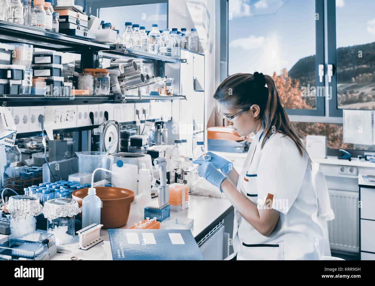 Jeune scientifique travaille en laboratoire biologique moderne, teinté de droit Photo Stock