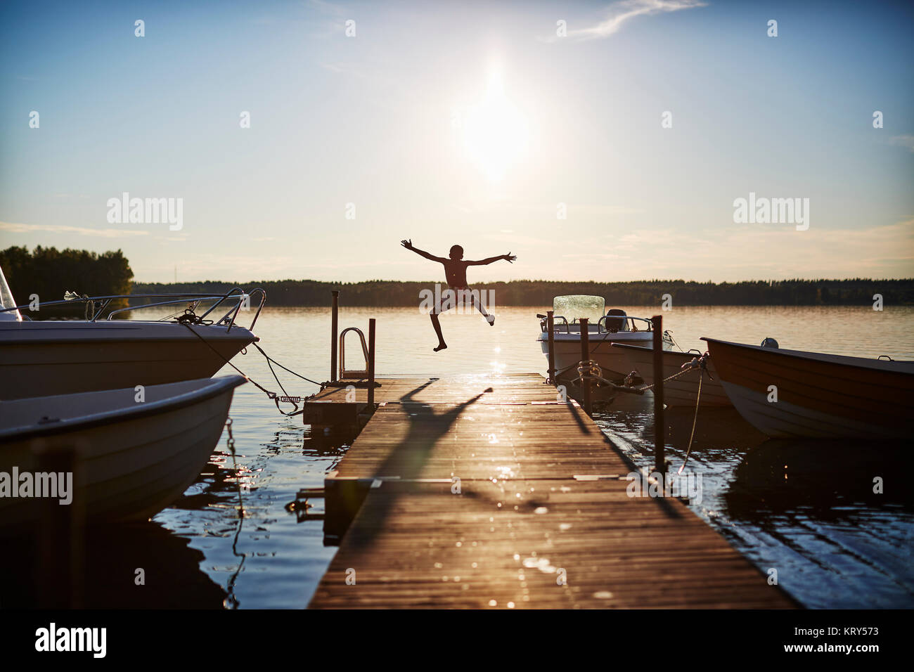 Boy jumping on a pier Photo Stock