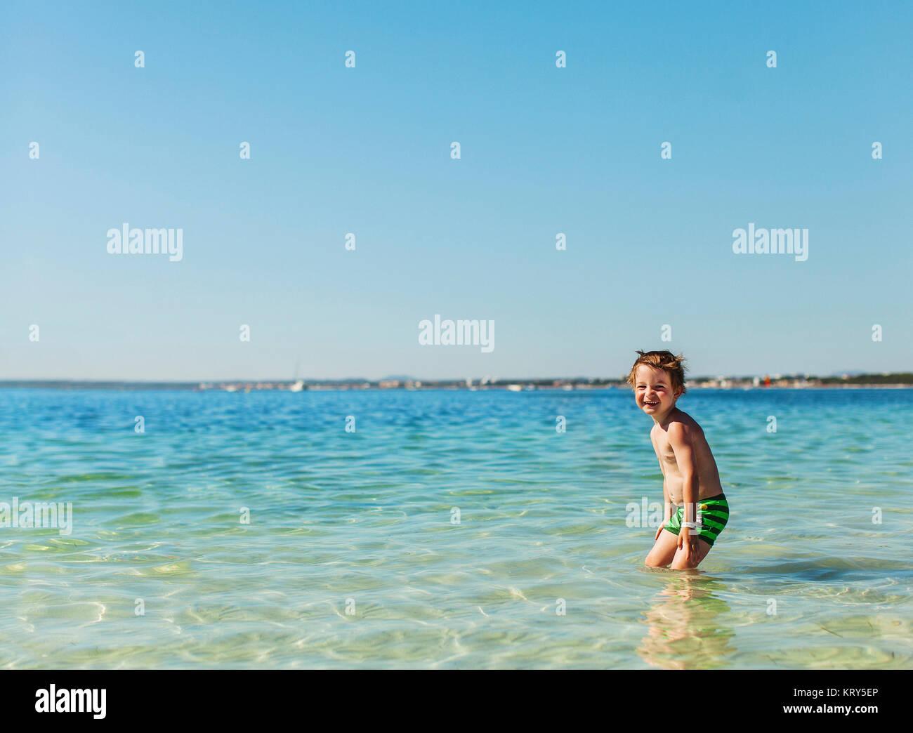 Un jeune garçon nager dans la mer Photo Stock