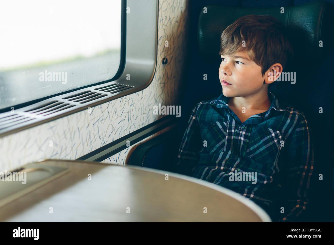 Un jeune garçon voyageant dans un train Photo Stock