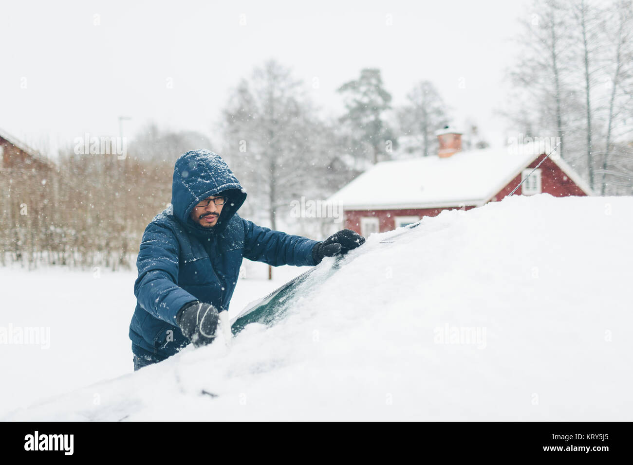 L'homme de sa voiture de la neige Photo Stock