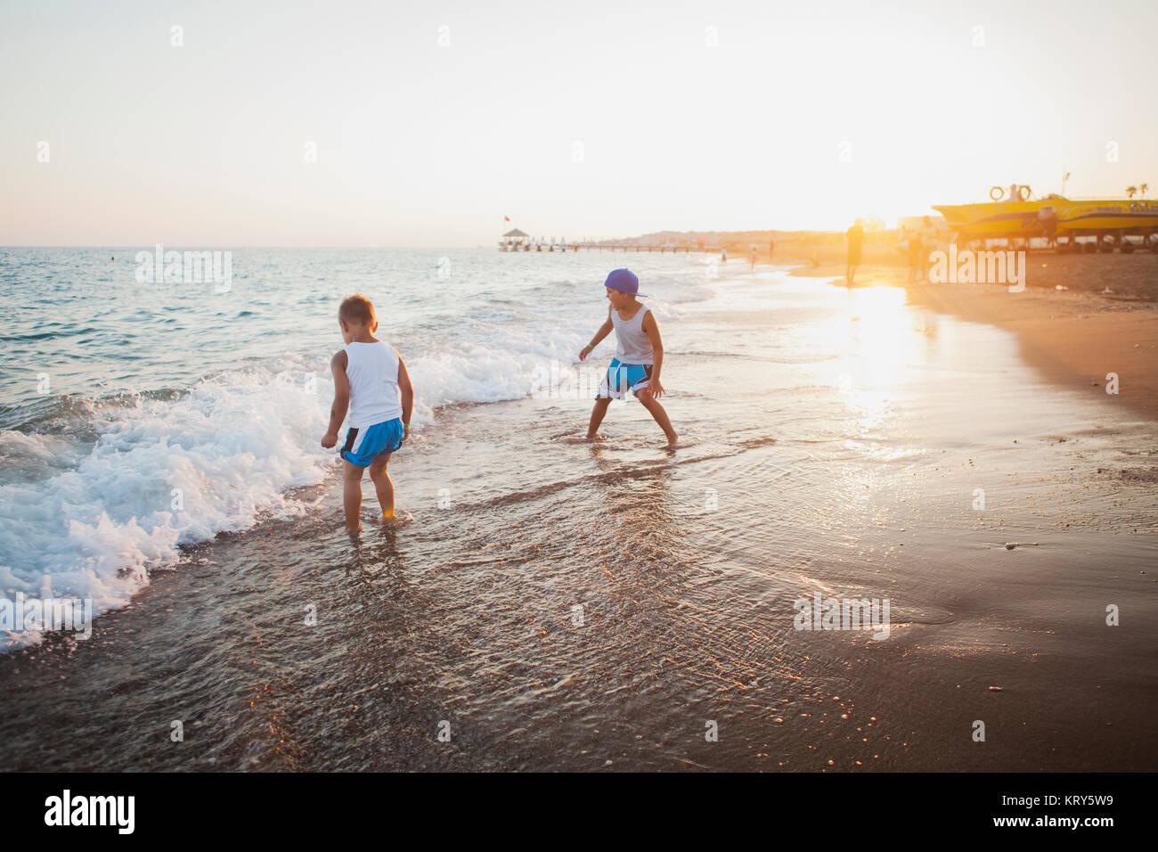 Enfants jouant dans les vagues sur une plage en Turquie Photo Stock