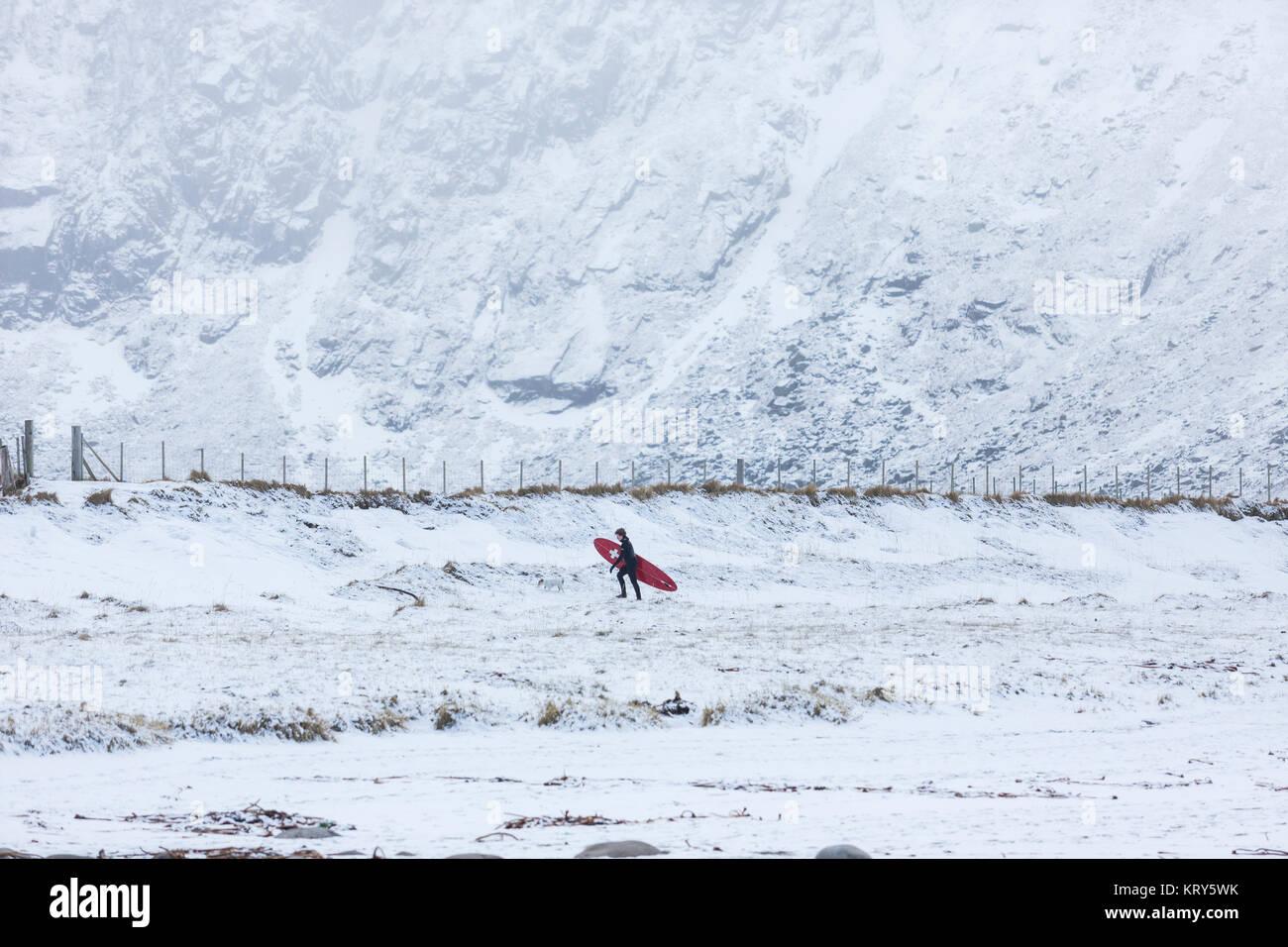Une personne qui porte une planche de surf sur sol enneigé en Norvège Photo Stock