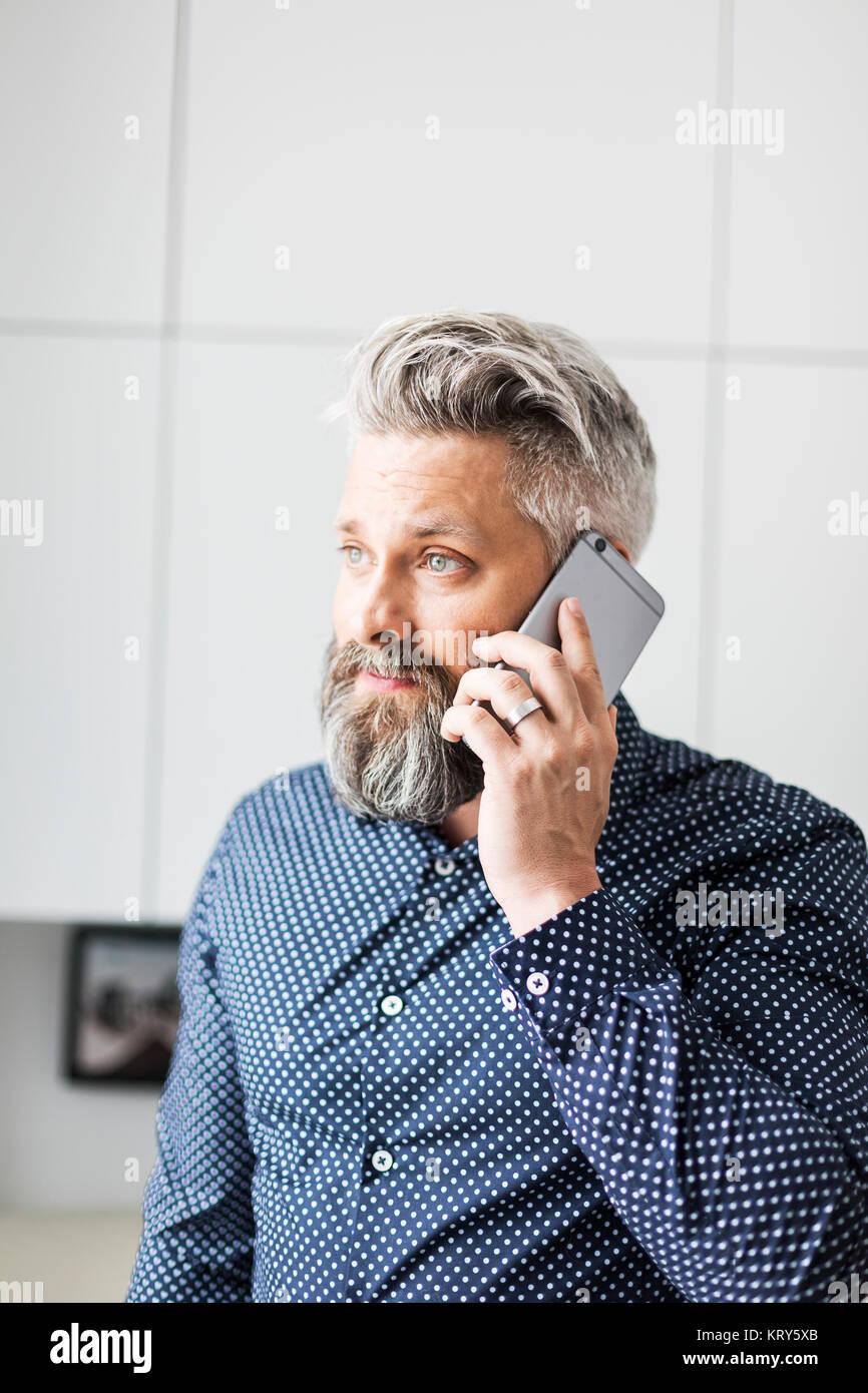 Un homme dans une chemise maculée de parler sur un téléphone cellulaire Photo Stock