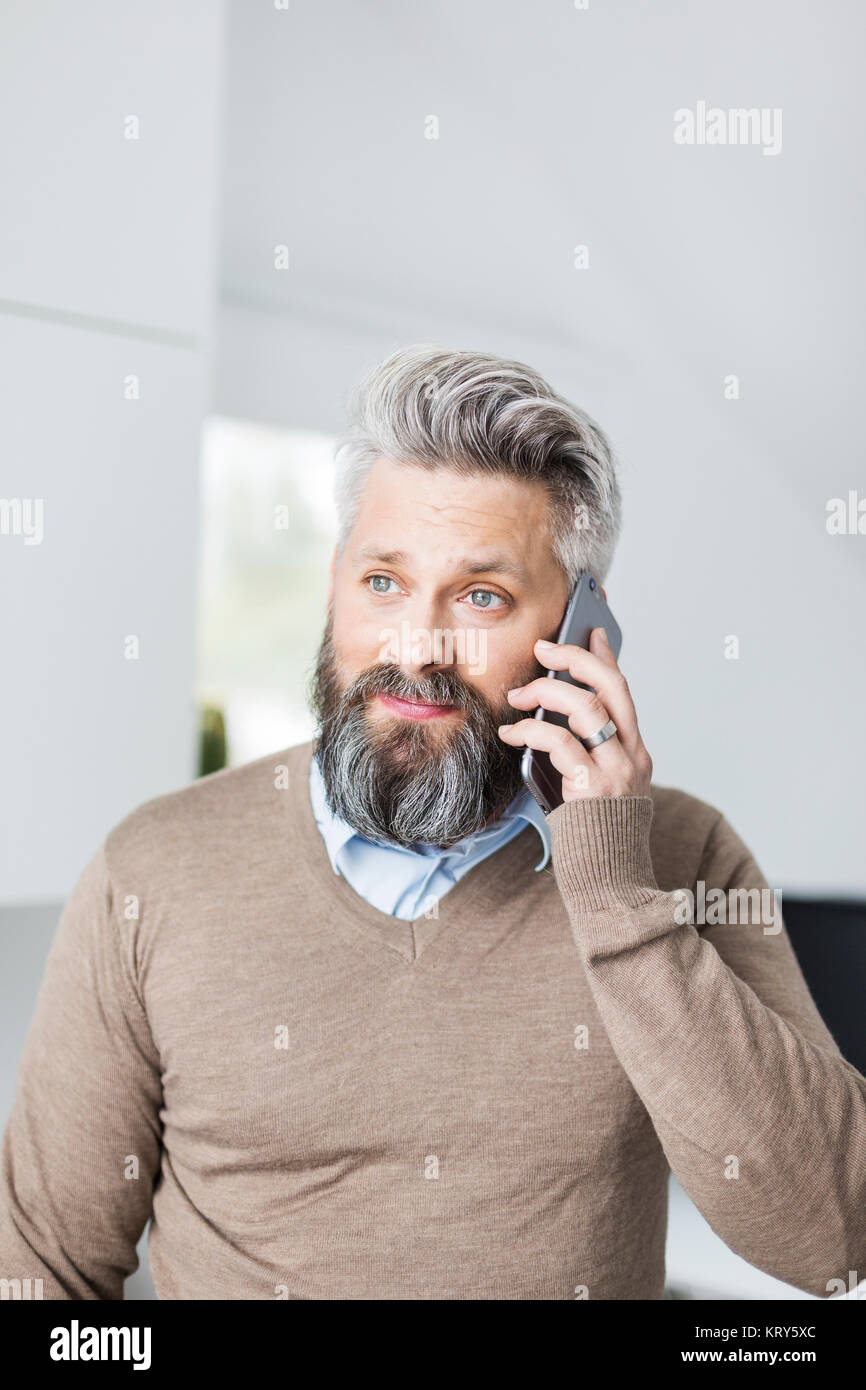 Un homme dans un pull marron talking on a cell phone Photo Stock