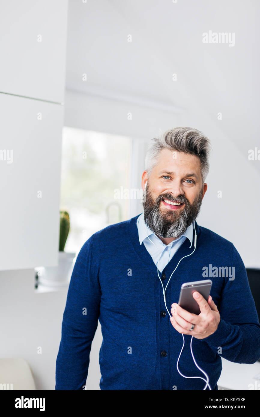 Un homme avec les casques dans l'écoute de son téléphone cellulaire Photo Stock