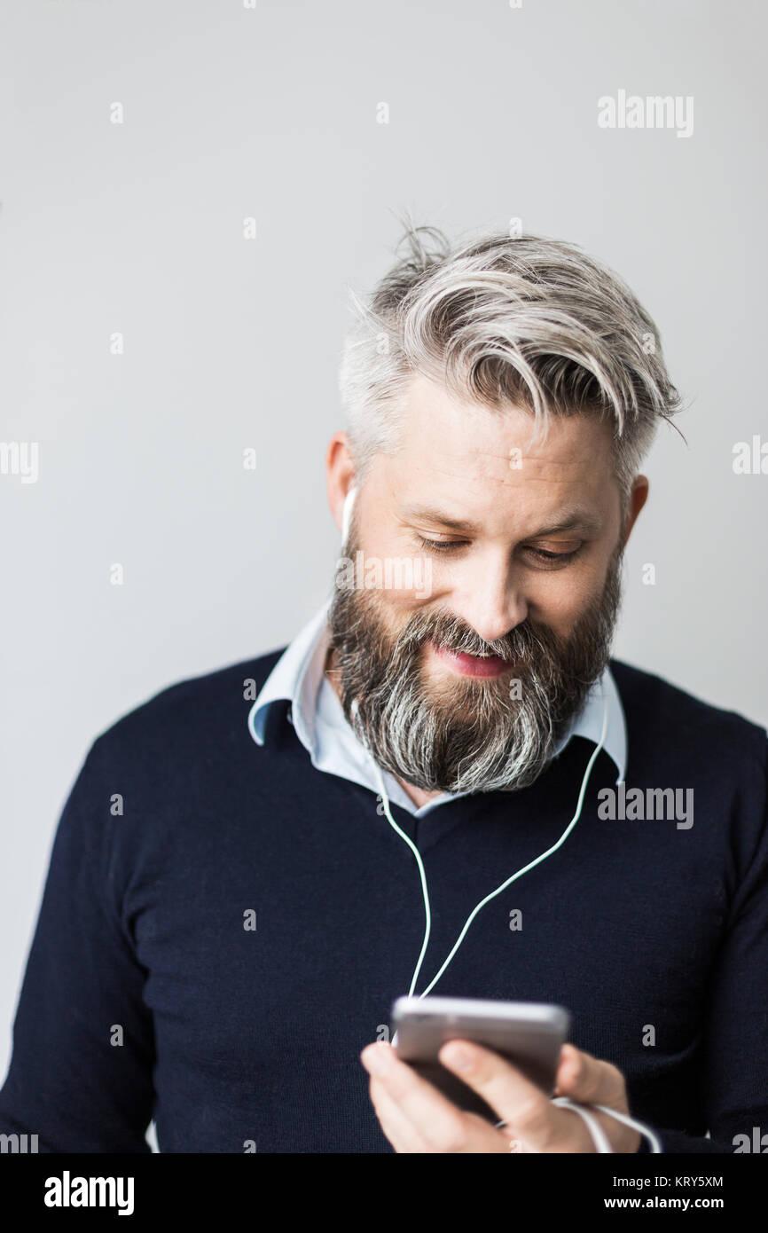 Un homme avec les casques dans l'écoute de son téléphone cellulaire Banque D'Images