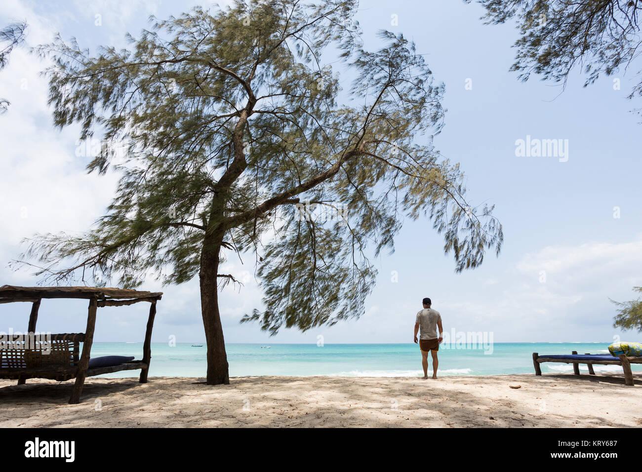 Homme debout sur la plage de Diani, Kenya Photo Stock