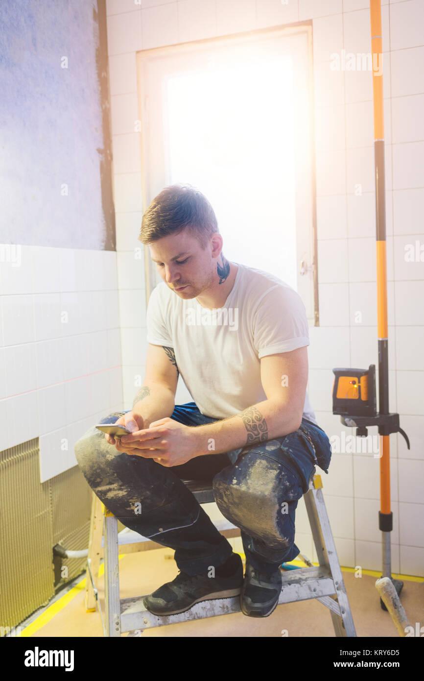 Homme tenant un téléphone intelligent dans la salle de bains Photo Stock