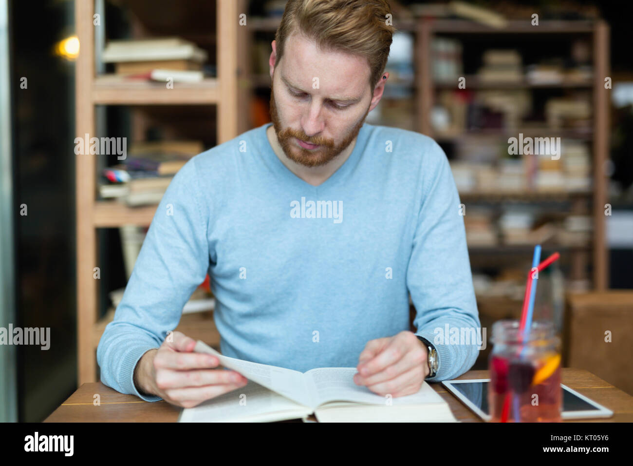 Young handsome student learning in coffee shop Photo Stock