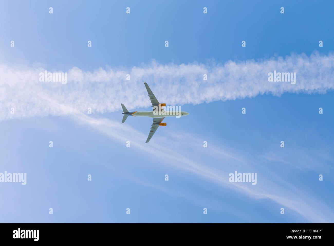 Un avion à réaction volant au-dessus d'un ciel bleu avec des traînées de vapeur Banque D'Images