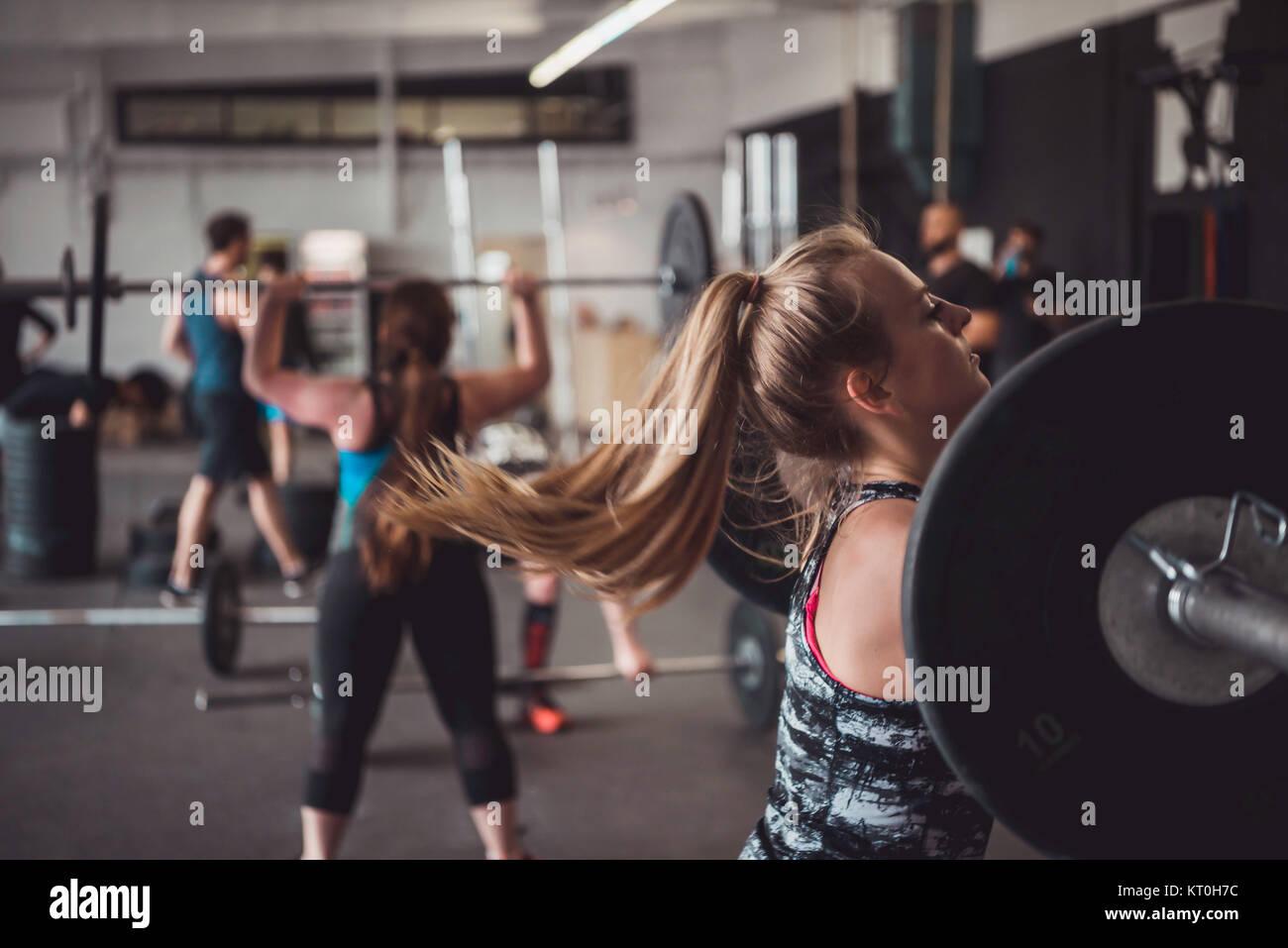 Les femmes et la formation de remise en forme. L'haltérophilie, l'élaboration et la formation polyvalente. Banque D'Images