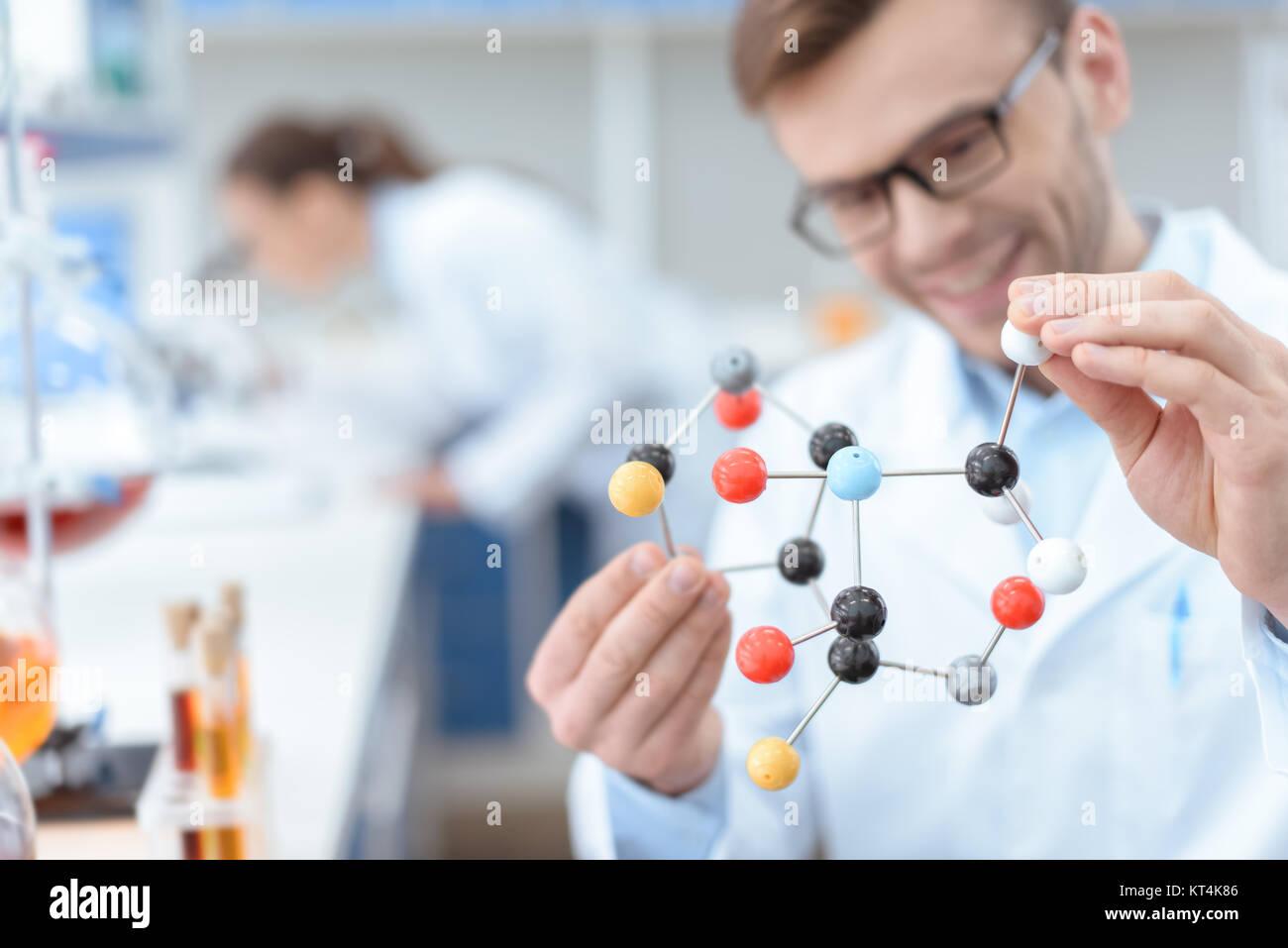 Smiling man scientifique à lunettes holding molecular model in lab Photo Stock