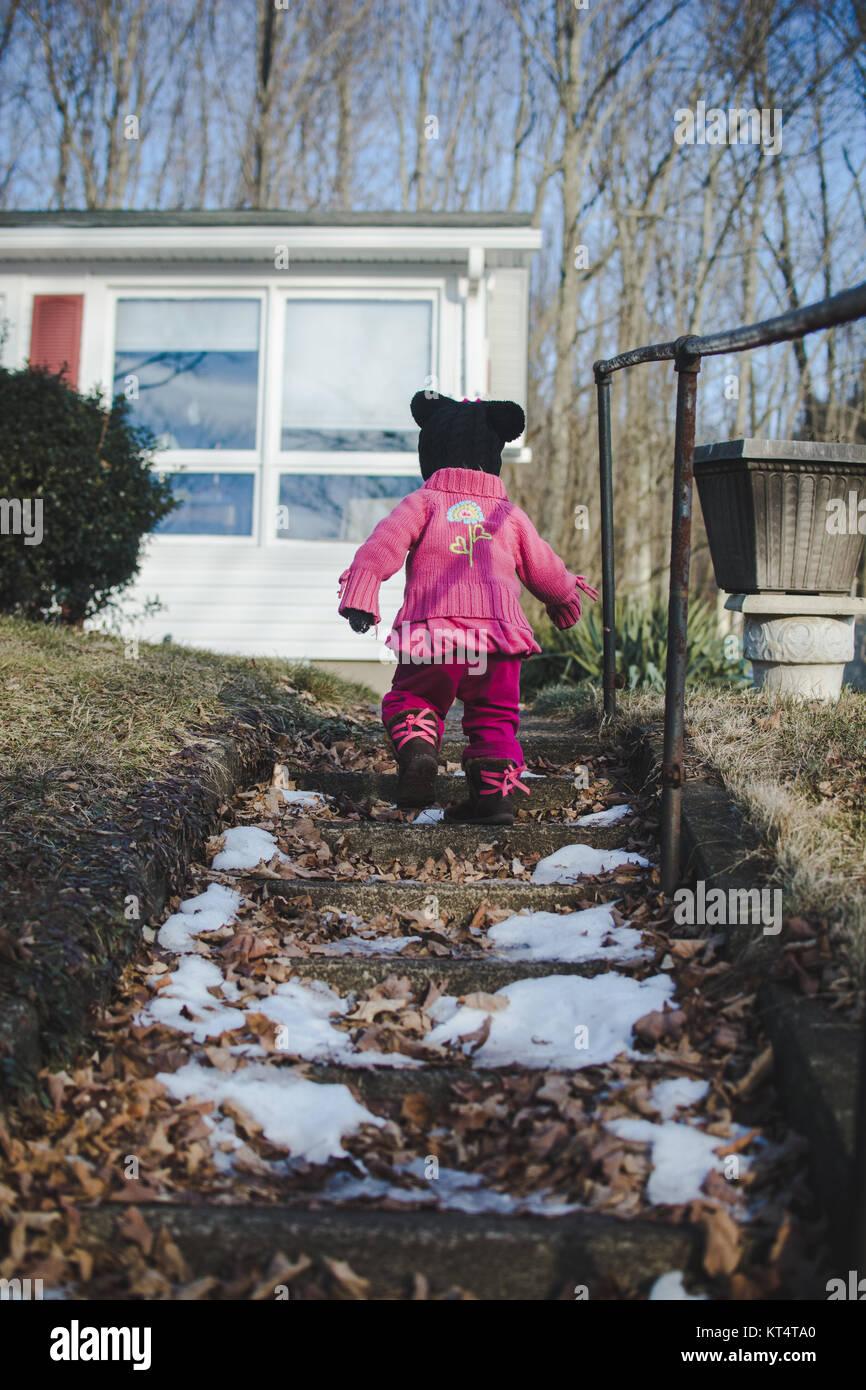 Un enfant monte en haut d'un escalier en pierre portant un chandail au cours de l'hiver Photo Stock
