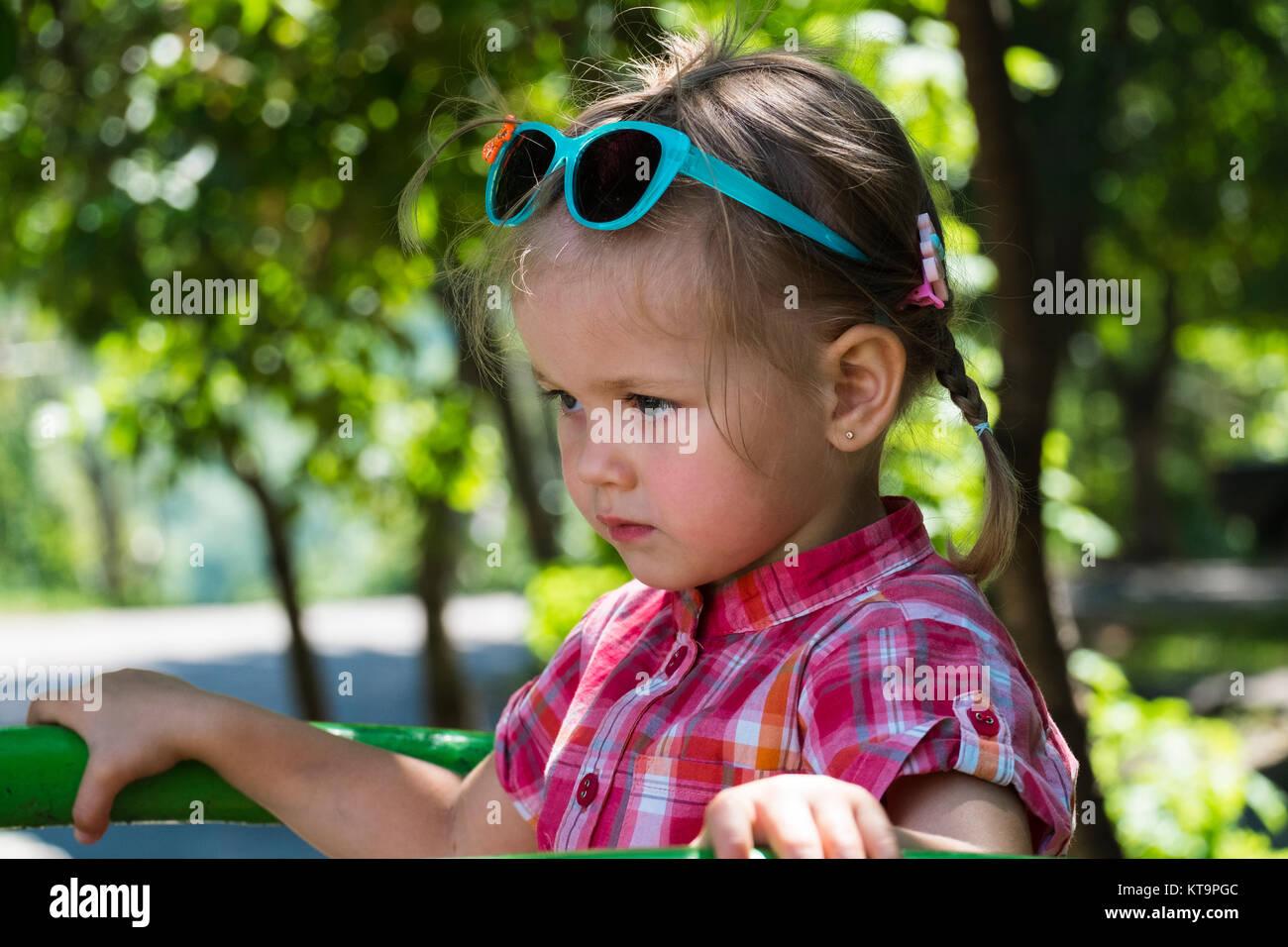 Petite fille avec des lunettes de soleil sur sa tête se trouve dans un demi- eb5f02903684