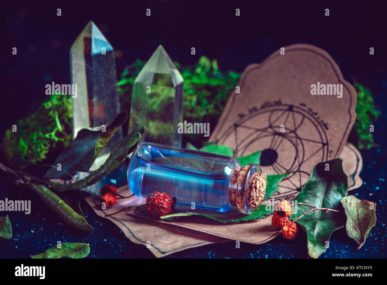 Flacon de potion avec des ingrédients, des herbes, des mousses et des cristaux dans une scène magique. Photo Stock