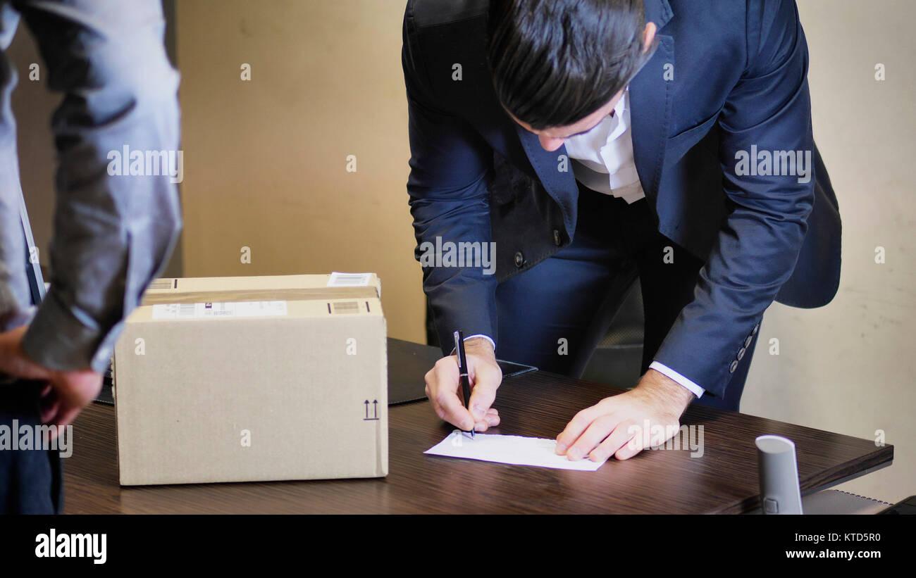 Portrait dans son bureau et à la parcelle à livré par courrier, réception signature illisible Photo Stock