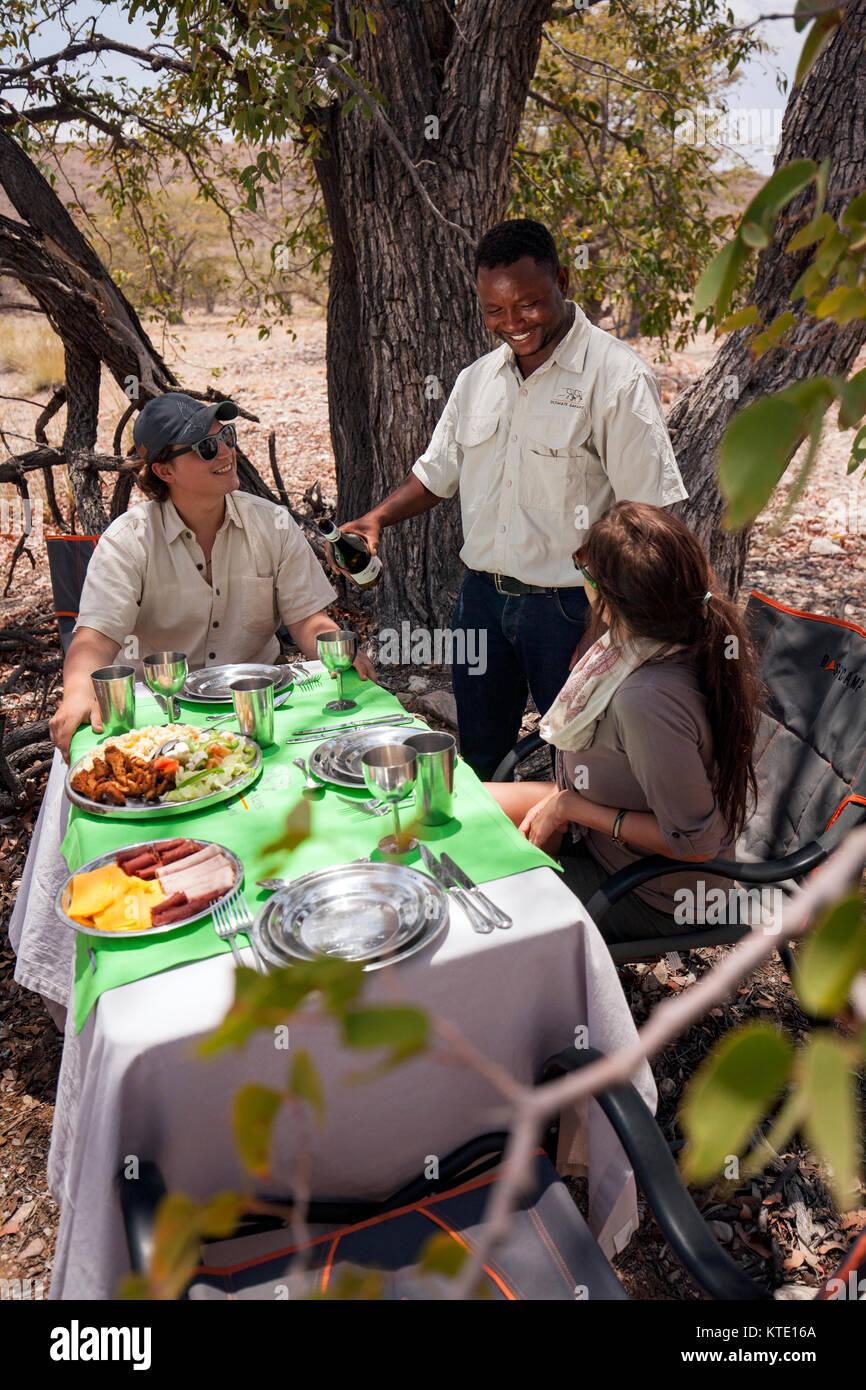 Couple enjoying déjeuner pique-nique à l'Huab sous toile, Damaraland, Namibie, Afrique Photo Stock