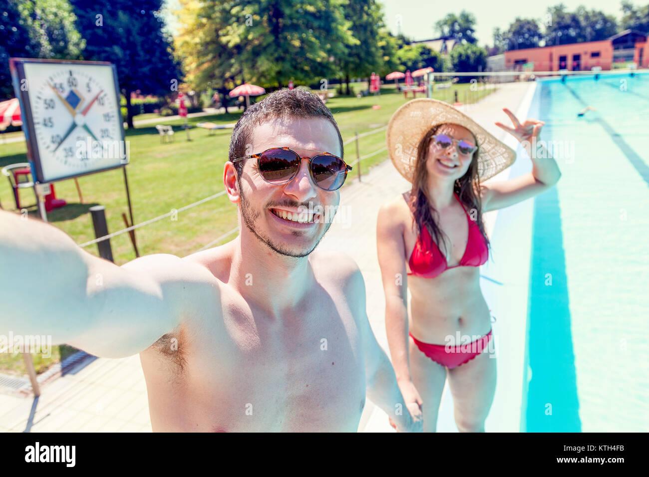 Jeune couple d'amoureux au bord de la piscine prend un maillot en selfies. Concept de jeunes s'amusant en Photo Stock
