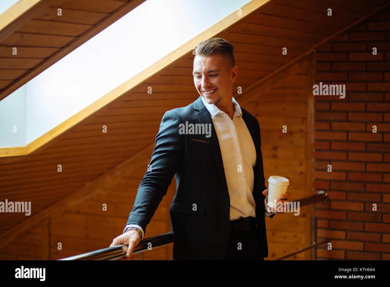 Handsome businessman de boire du café à la maison et à l'écart Photo Stock