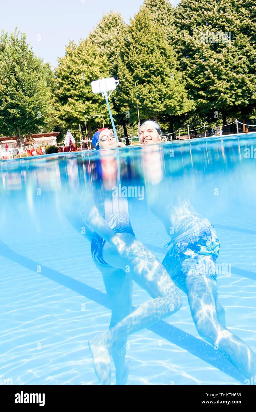Jeune couple aimant prend un sous-marin selfies dans la piscine. Concept de jeunes s'amusant en été Photo Stock
