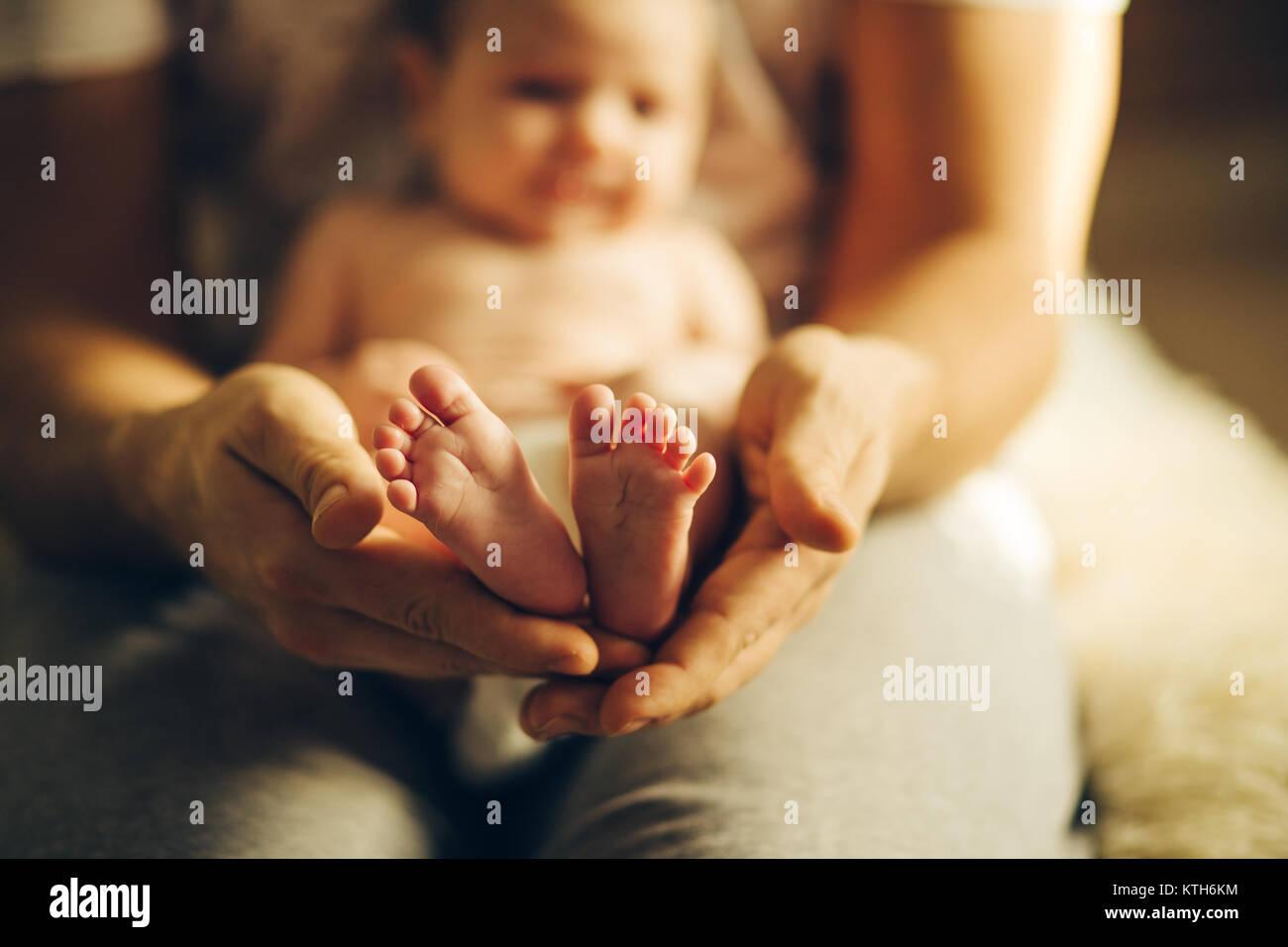 Baby les mains. Les pieds de bébé nouveau-né sur les mains Photo Stock