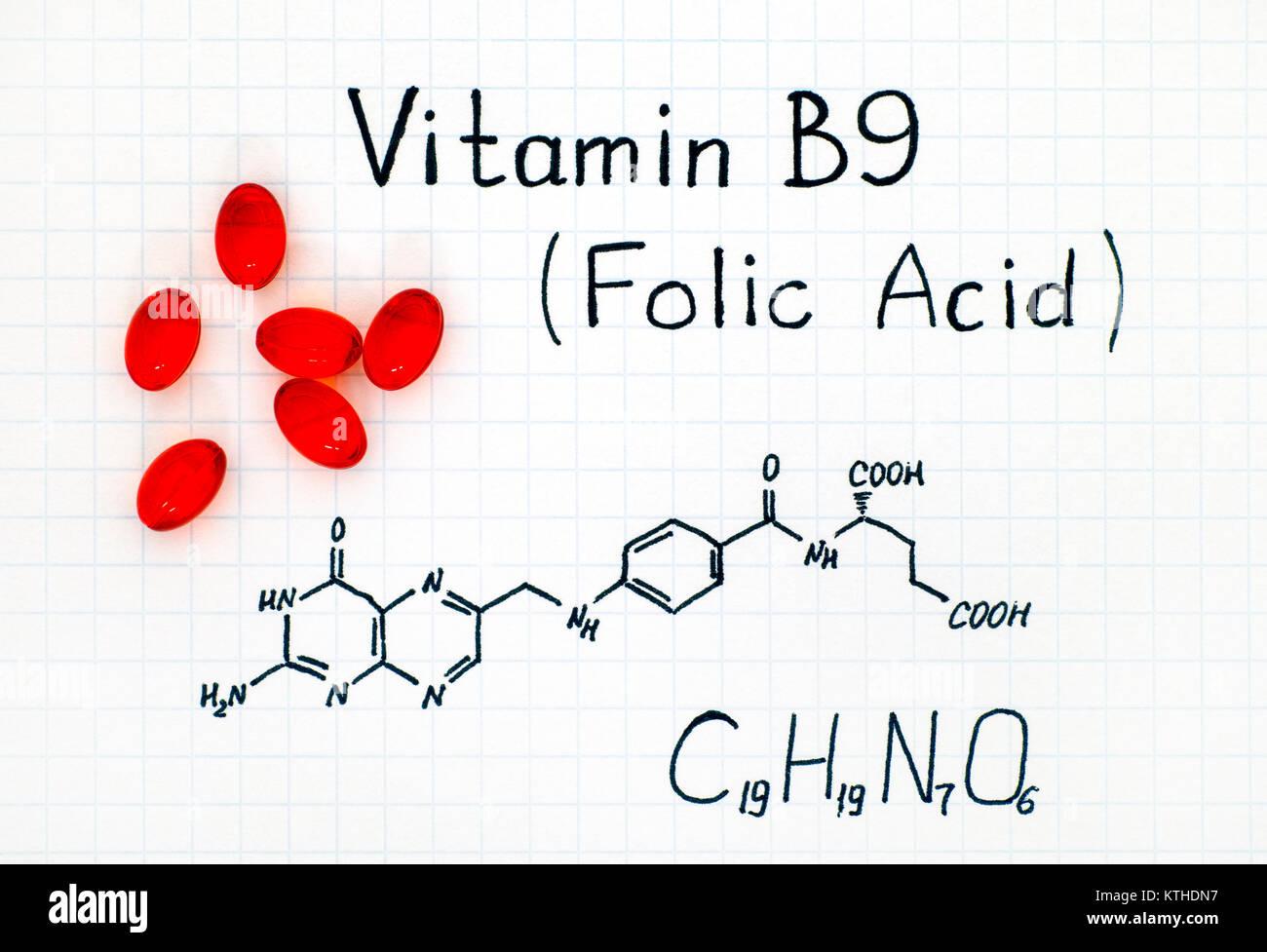Formule chimique de la vitamine B9 (acide folique) avec red pills. Close-up. Photo Stock