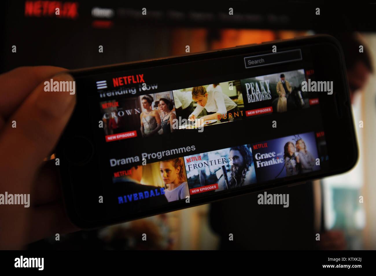 Le site web de Netflix sur un téléphone et écran de l'ordinateur Photo Stock