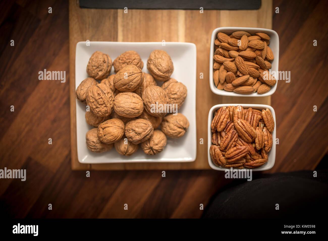 Un choix sain et nutritif des fruits secs sur un sol en bois servant de sélection avec les noix, pacanes, amandes Photo Stock