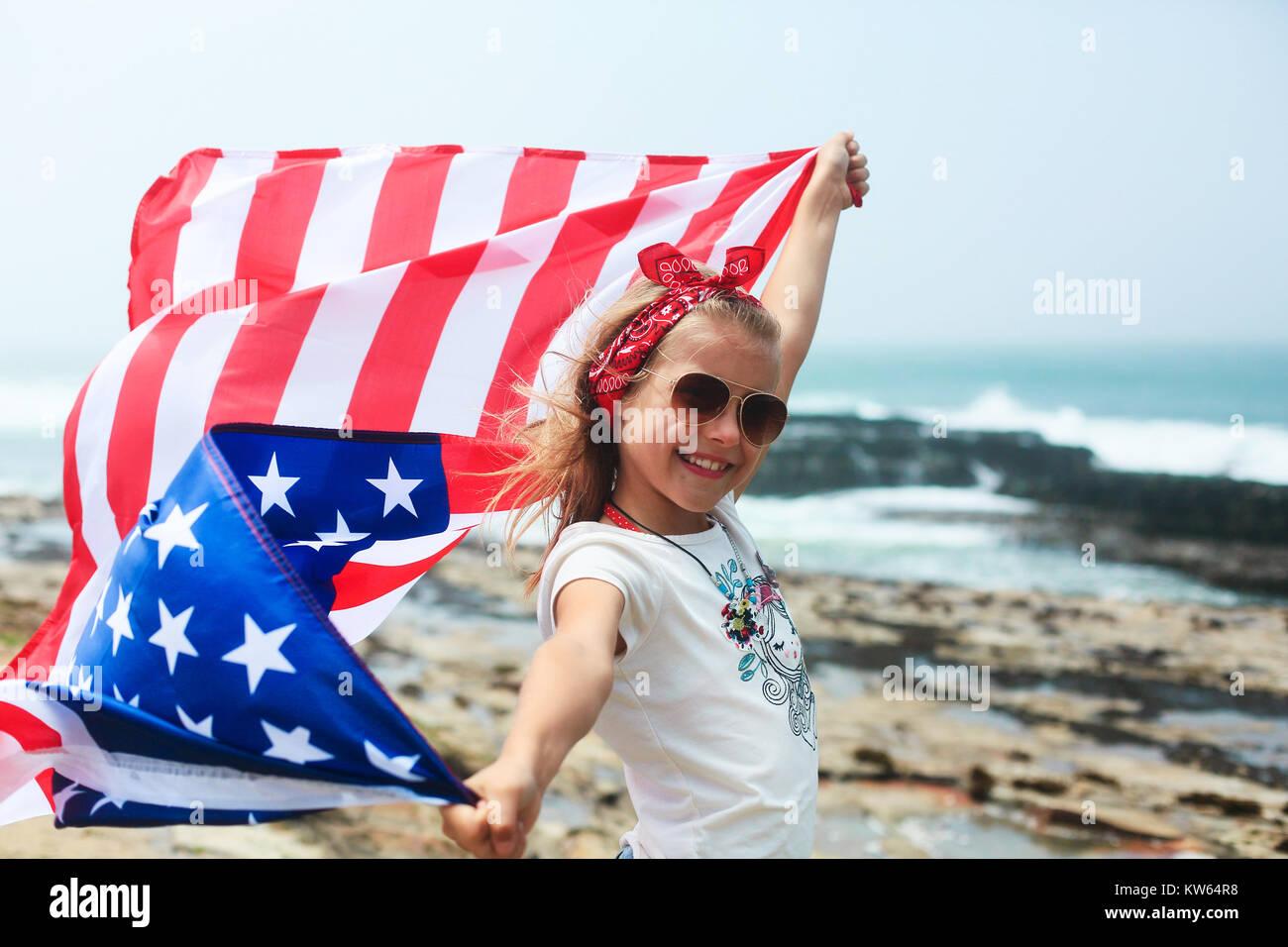 Smiling girl détient agitant drapeau américain USA Le jour de l'indépendance (4 juillet) Banque D'Images