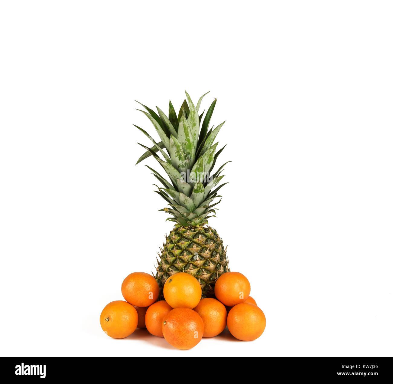 Sur un fond blanc il y a un gros ananas mûrs et plusieurs fruits mandarin Photo Stock
