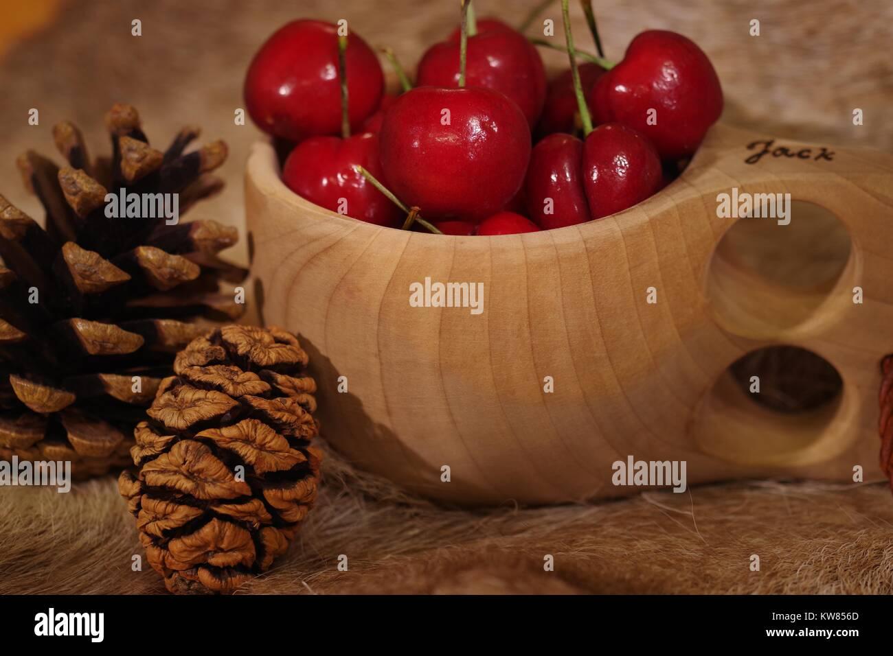 Les cerises dans une coupelle en bois finlandais Kulsa sur une fourrure de renne avec cocottes. La vie encore scandinaves et la saine alimentation. L'hiver 2017. Banque D'Images
