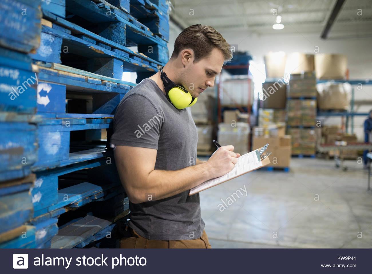 Travailleur masculin avec presse-papiers à l'entrepôt de distribution Photo Stock