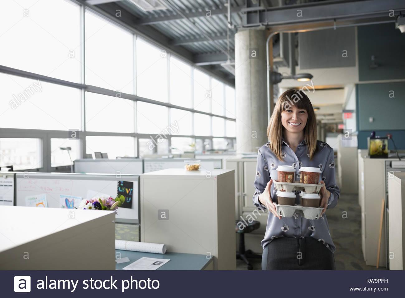Portrait smiling businesswoman généreux,les porteéchantillons de café in office Photo Stock