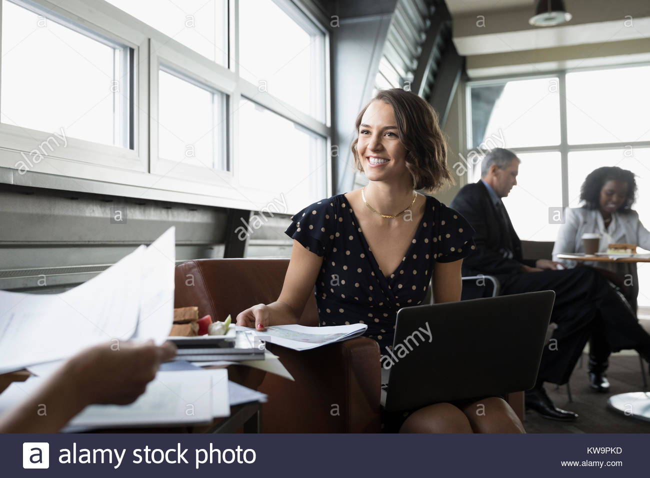 Smiling,confident businesswoman with paperwork using laptop in business lounge Photo Stock