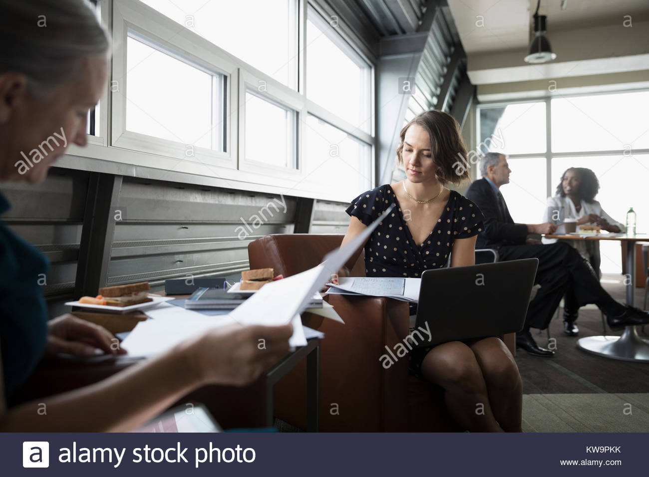 L'accent businesswoman reviewing paperwork at laptop in business lounge Photo Stock