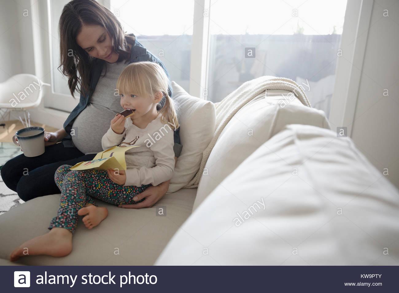 Femme enceinte et enfant daughter enjoying snack sur salon canapé Photo Stock