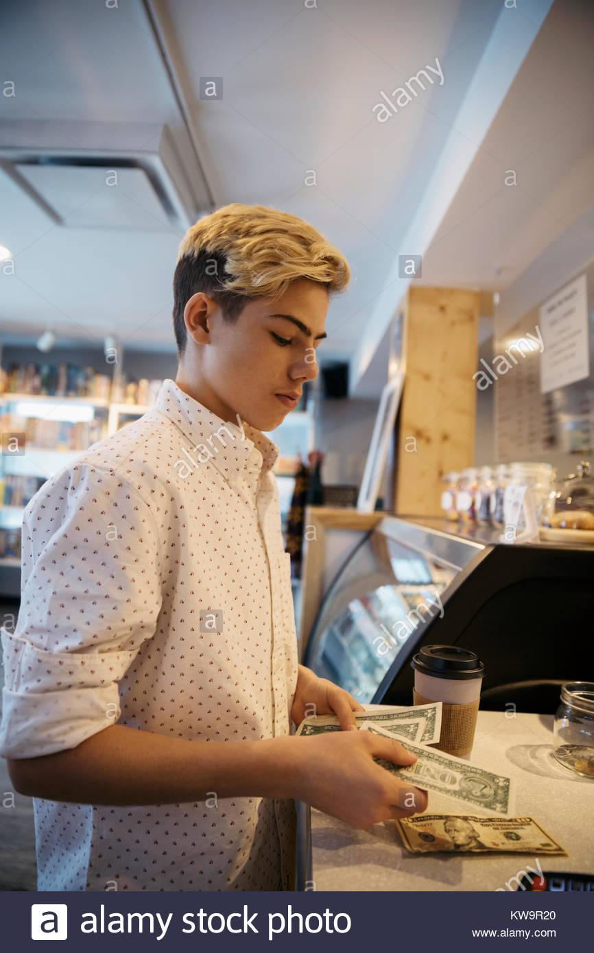 Caucasian boy tween payer en argent comptant au comptoir de café Photo Stock
