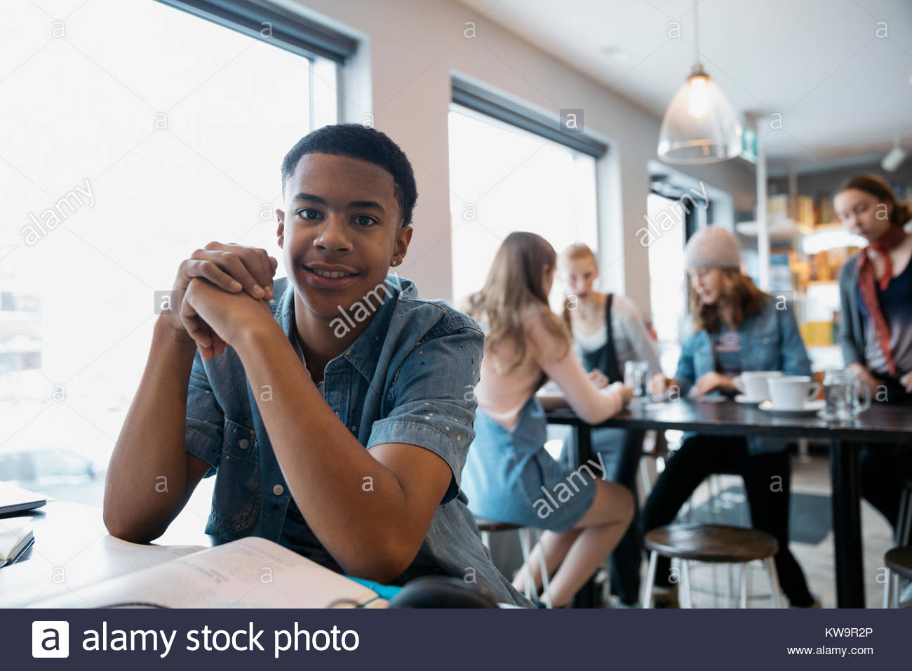 Portrait confiant African American boy high school student studying in cafe Photo Stock