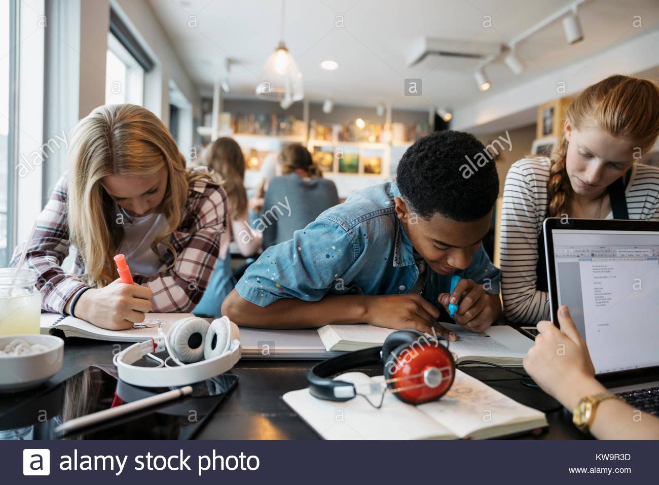 Les élèves du secondaire étudiant au cafe table Photo Stock
