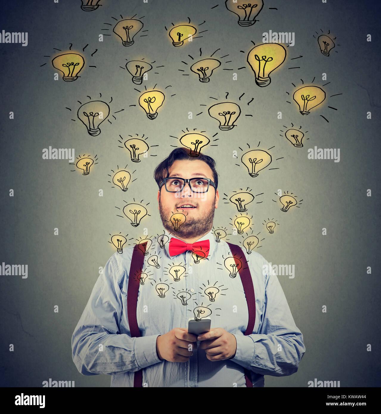 Jeune homme excité holding smartphone avec partage des idées brillantes à contenu. Photo Stock
