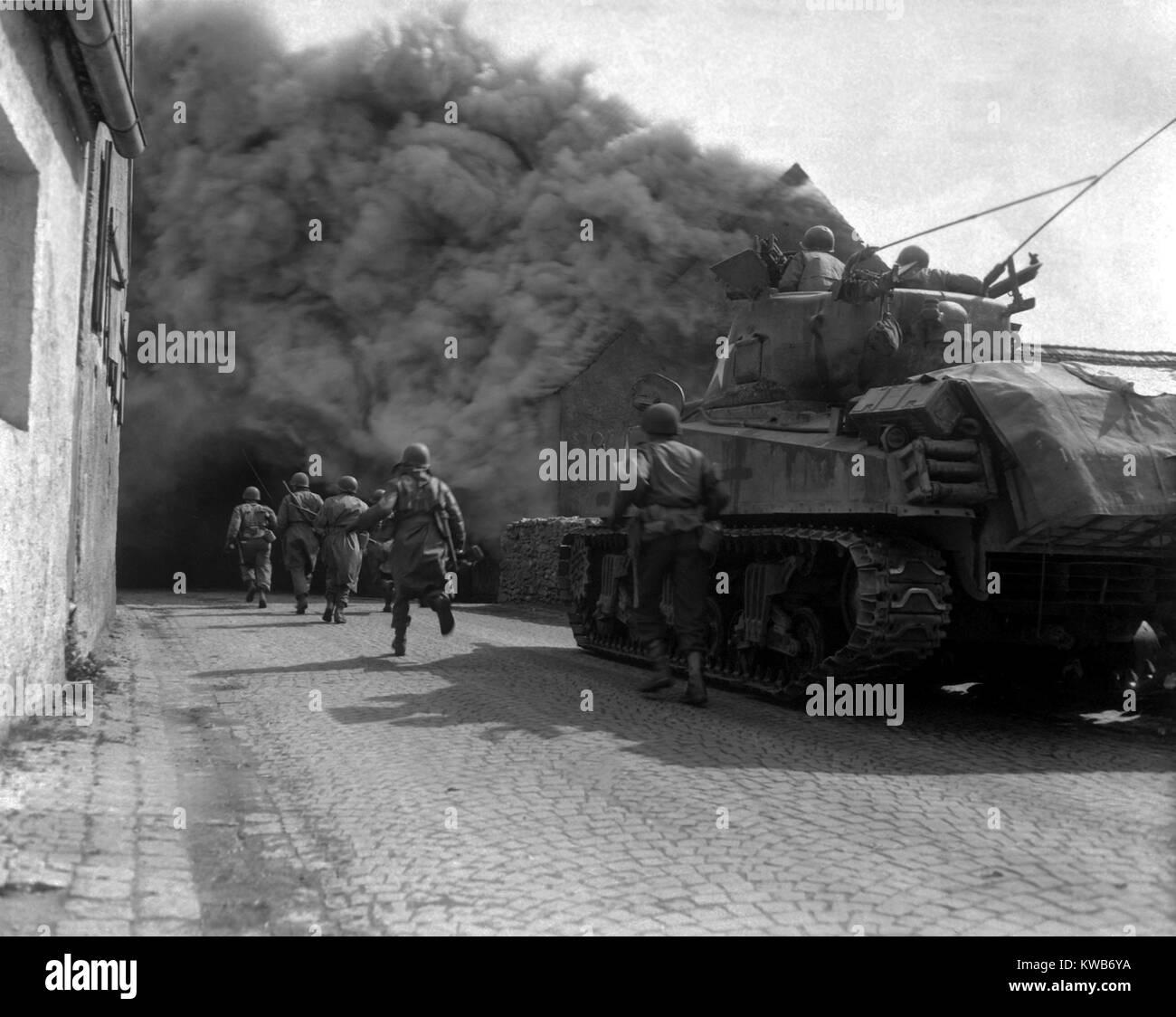 Les fantassins américains dans les rues enfumées de Wernberg, Allemagne. 55e Bataillon d'infanterie blindée et le Banque D'Images