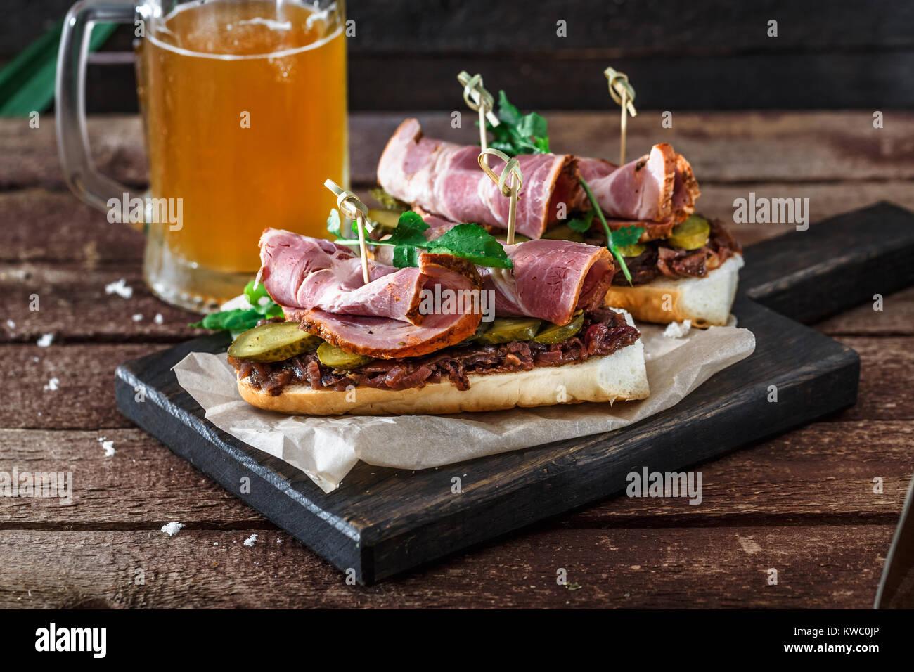 Sandwiches avec de la viande fumée, confiture d'oignons et de bière Photo Stock