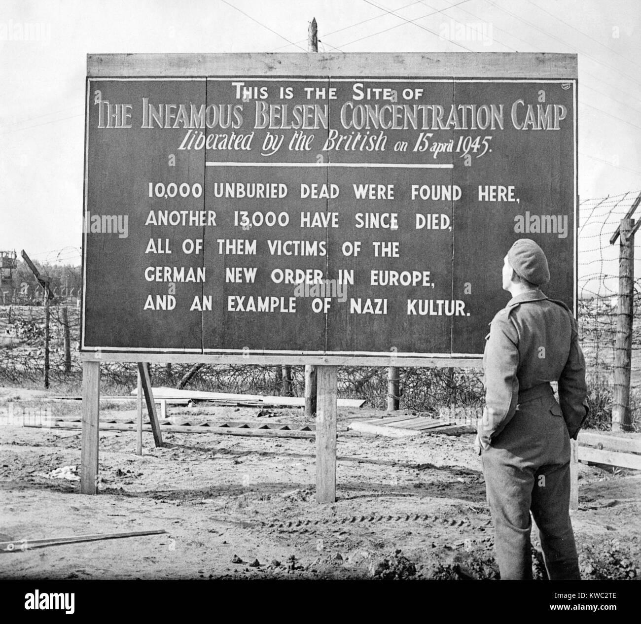 Soldat britannique se distingue par un panneau posé à l'emplacement de la Camp de concentration de Belsen, 1945. Banque D'Images