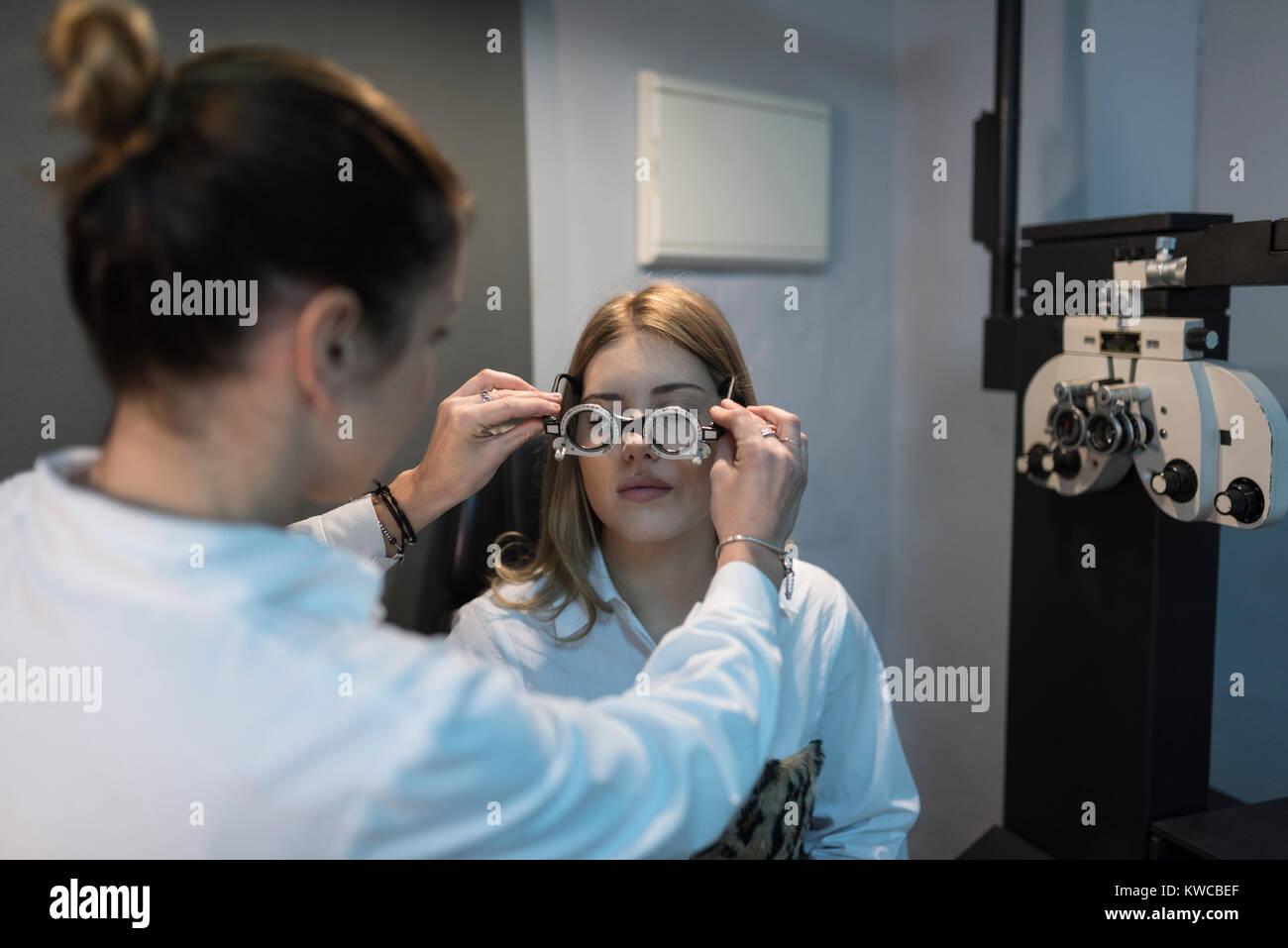 Femme en optométrie essaie d'essai sur le bâti d'essai au client Photo Stock