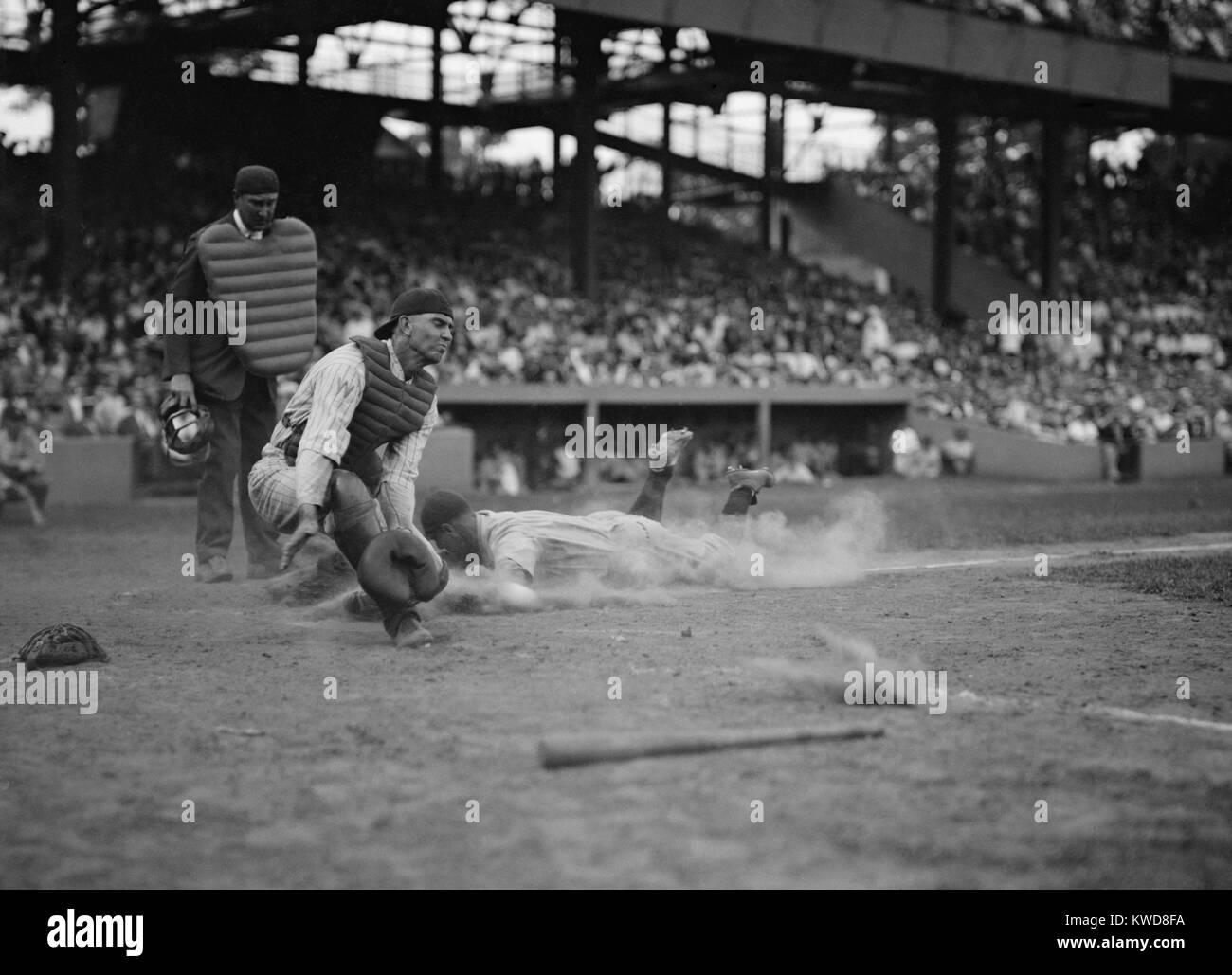 Lou Gehrig des Yankees notes comme Joe Harris' jeter s'éloigne de catcher Hank Severeid des sénateurs. New York Banque D'Images